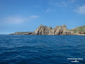 Kayak Fishing at Porthcurno - Looking towards Logan Rock on a calm day